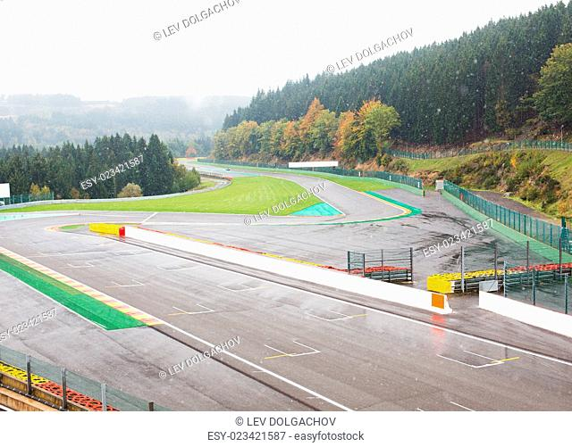 motosports, extreme, weather and race concept - close up of speedway track or road and snow