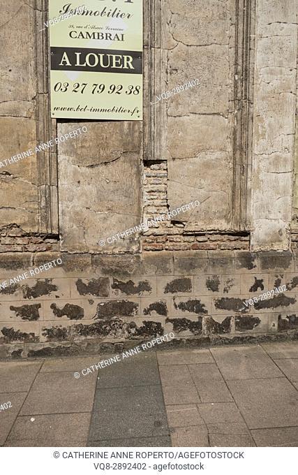 Deteriorating building with crumbling plasterwork revealing brick interior advertised for rent by elegant copperplate sign in the historic centre of Cambrai