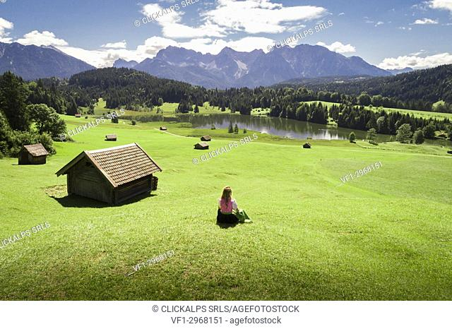 A girl in typical dress looks at the Geroldsee. Gerold, Garmisch Partenkirchen, Bayern, Germany
