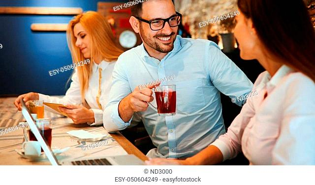 Happy young colleagues from work socializing in restaurant