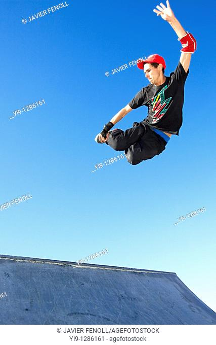 Young man jumping in mid air wearing inline skates