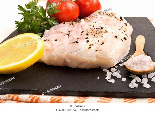 hake fillet on a slate plate with coarse sea salt, a slice of lemon, parsley and fresh, wet tomato