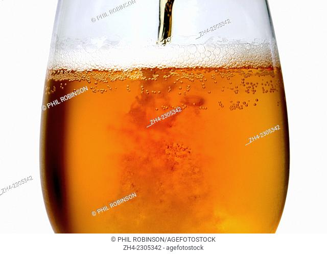 Beer being poured into a large glass