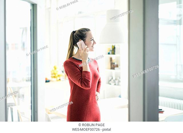 Smiling woman on the phone looking out of window