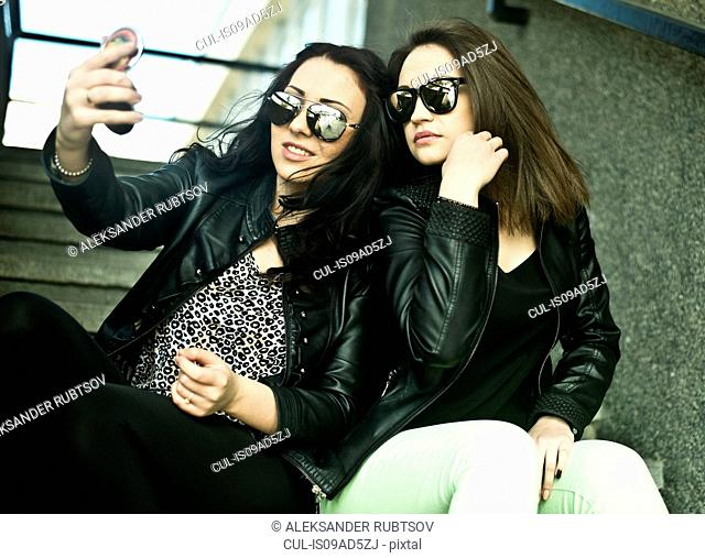 Two young woman making self portrait on mobile phone
