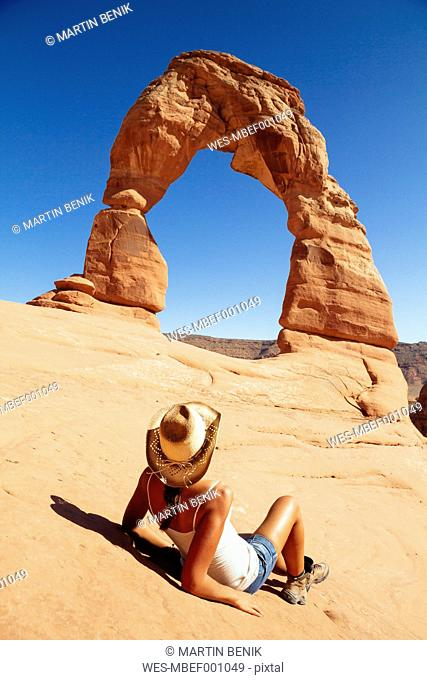 USA, Utah, woman relaxing in front of Delicate Arch at Arches National Park, back view