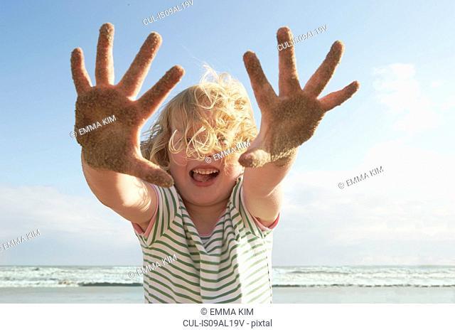 Girl holding up sandy hands on breezy beach, Camber Sands, Kent, UK
