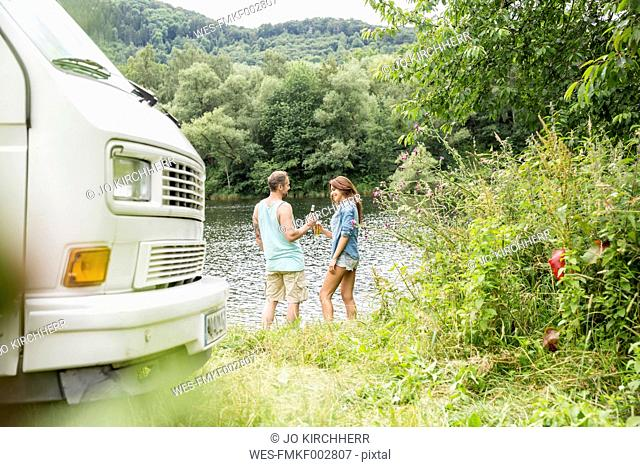 Couple with van at lakeside clinking beer bottles