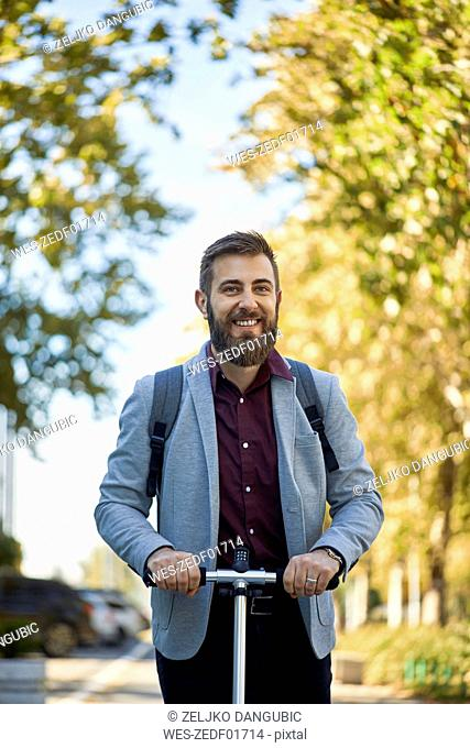 Portrait of smiling businessman with scooter