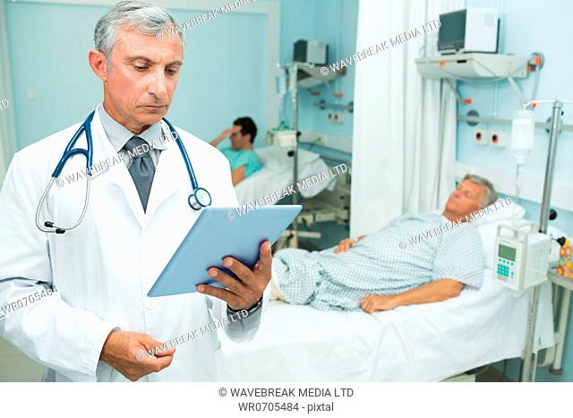 Doctor holding a tactile tablet while standing in a hospital bed ward