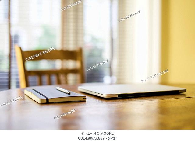 Notebook pen and laptop on dining room table