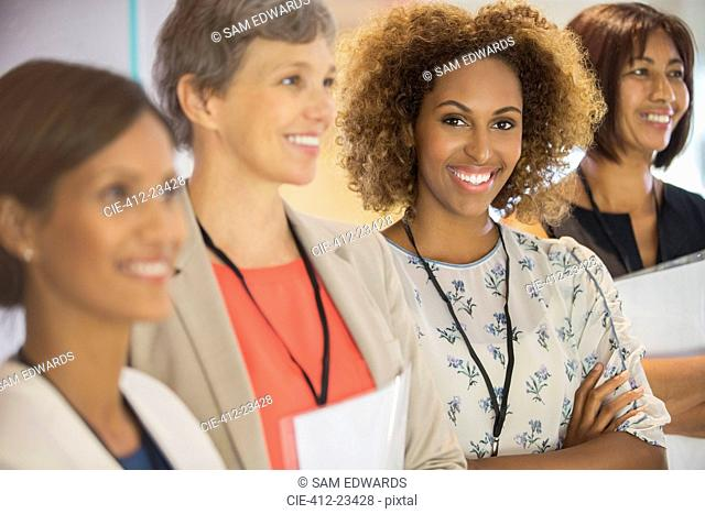 Portrait of businesswoman, looking at camera and standing with her colleagues