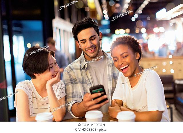 Young friends using cell phone, texting and laughing at cafe