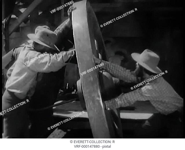 Men moving large wooden wheel
