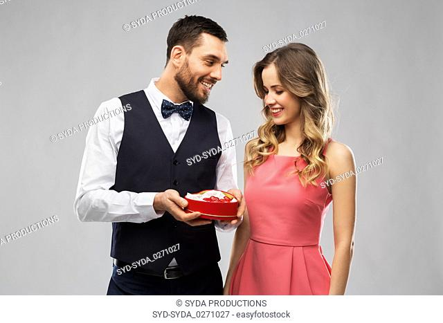 happy couple with chocolate box in shape of heart
