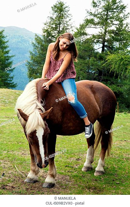 Young woman sitting on palomino horse, Sattelbergalm, Tyrol, Austria