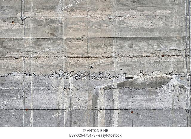 Concrete wall texture with wooden pattern impress from wooden form board shuttering and with sags of cement, close up