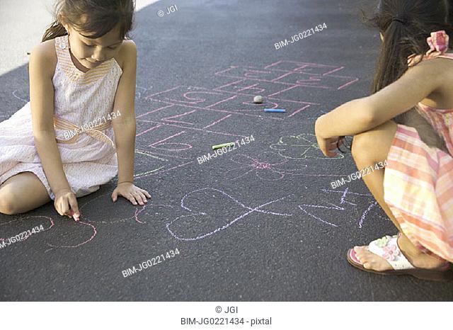 Two girls making chalk drawings