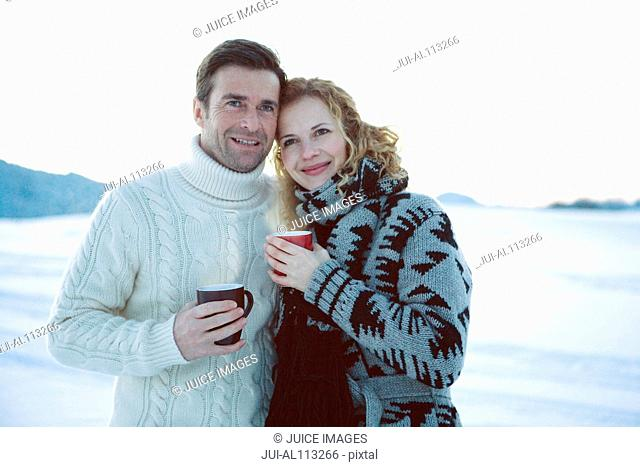 Couple holding hot drinks in winter, portrait