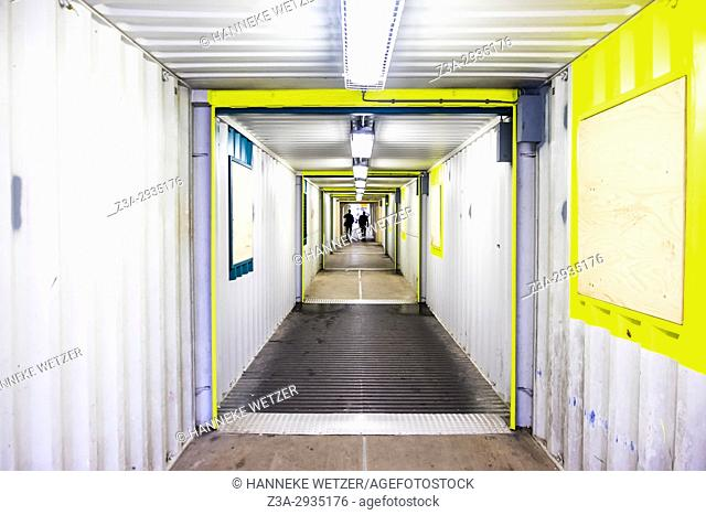 People walking through a temporary tunnel made out of sea containers