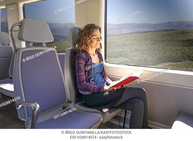 red hair smiling woman dressed in purple and blue, traveling by train sitting reading red open book