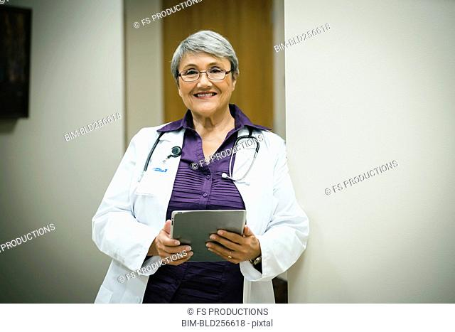Portrait of smiling mixed race doctor using digital tablet