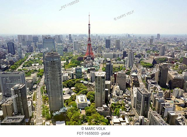 Aerial view of Tokyo Tower in city against sky on sunny day, Tokyo, Japan