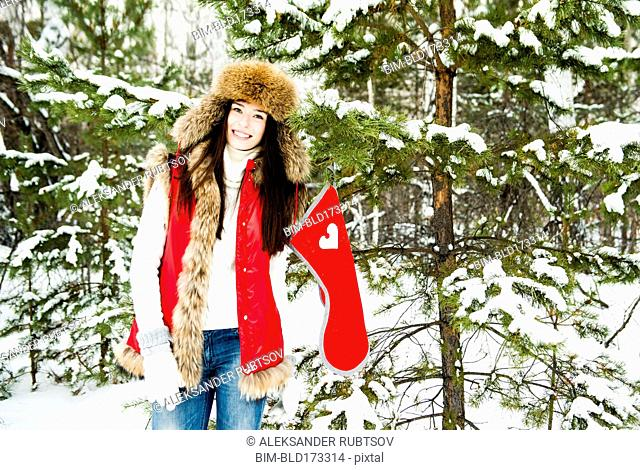 Caucasian girl hanging Christmas stocking on snowy tree