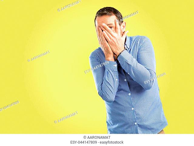 Handsome middle age man smiling having shy look peeking through her fingers, covering face with hands looking confusedly broadly