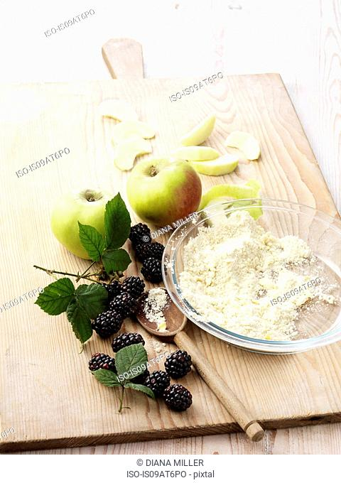 Ingredients for apple and blackberry crumble on whitewashed wooden table