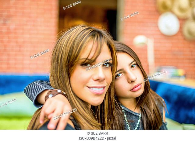 Portrait of girl with arm around mother in urban setting