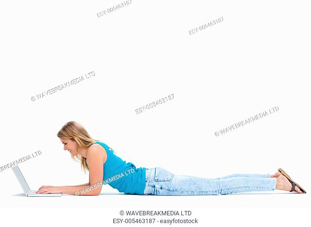 A woman is lying on the ground typing on her laptop