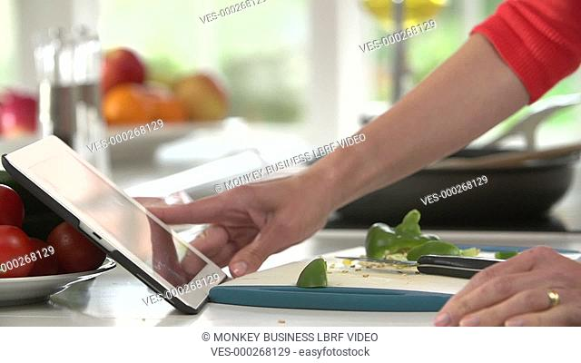 Woman checks recipe on digital tablet before stirring frying pan.Shot on Sony FS700 in PAL format at a frame rate of 25fps