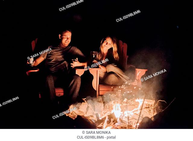 Couple sitting by camp fire, Algonquin Park, Canada