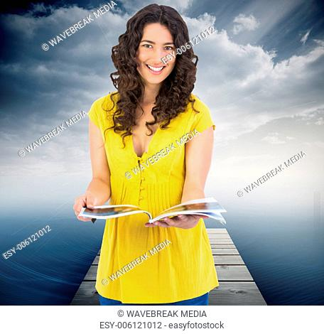 Composite image of cheerful curly haired brunette reading magazine