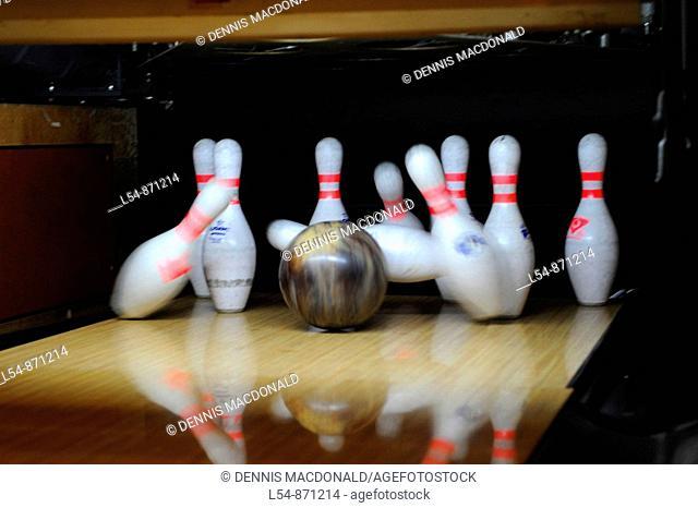 Black Bowling Ball Hitting White Bowling Pins