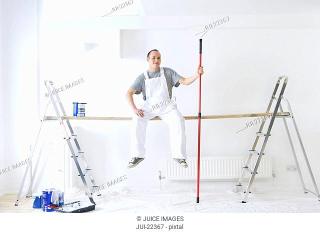 Man sitting on wood plank between ladders and holding paint roller