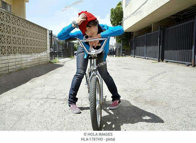 Young woman sitting on a bicycle and scratching her head