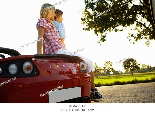 Couple sitting on their electric car