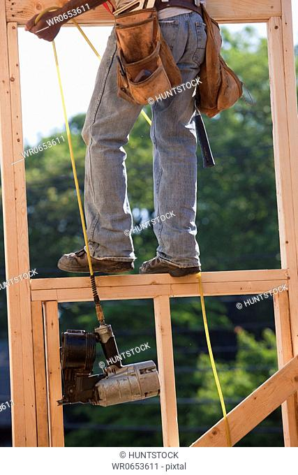 Carpenter pulling nail gun up to the second floor of a house under construction