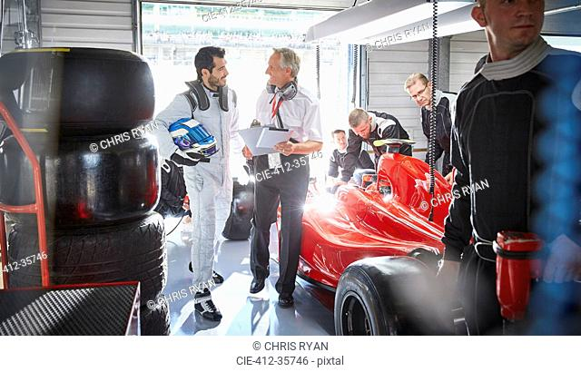 Manager and formula one race car driver talking in repair garage