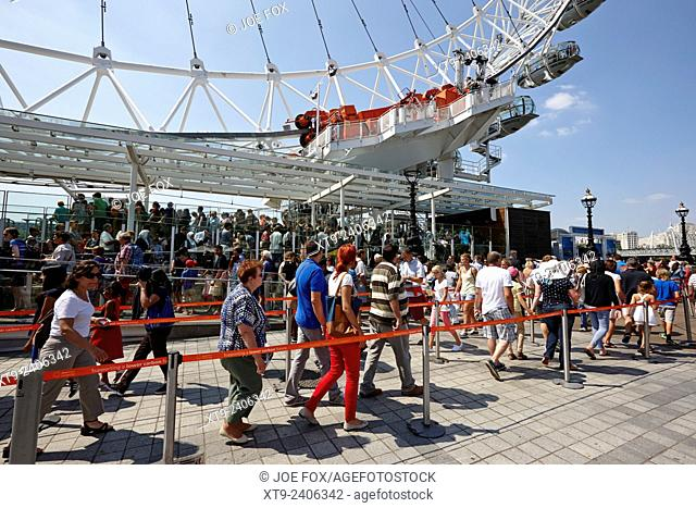 tourists queue to get into the london eye tourist attraction London England UK