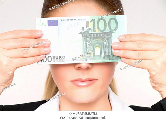 Gorgeous blonde woman holds 100 euro banknotes fanned in her hands