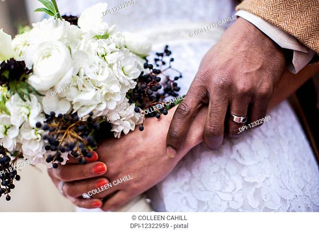A bride and grooms hands together with a view of the wedding dress and flower bouquet; Portland, Oregon, United States of America