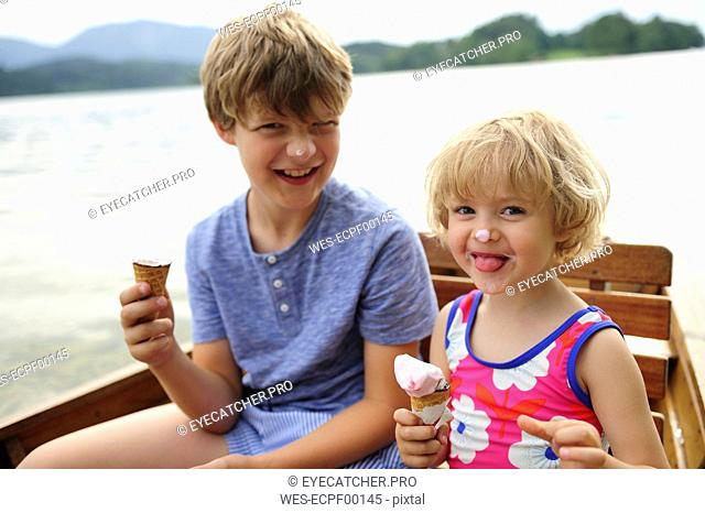 Portrait of little girl sitting in rowing boat with her brother eating icecream