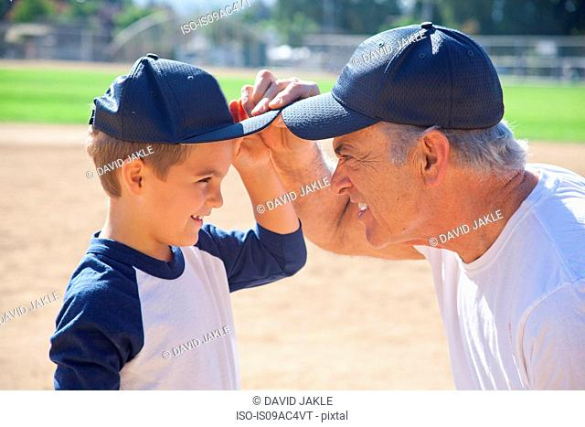 Boy and grandfather in baseball caps, face to face