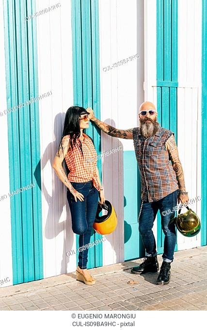 Mature hipster couple leaning against striped wall, portrait