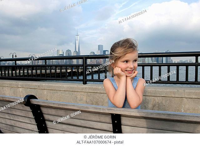Little girl resting on pier near New York City, New York, USA