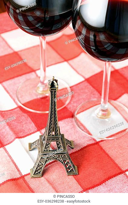 Little Eiffel tower and a pair of wineglasses on the table