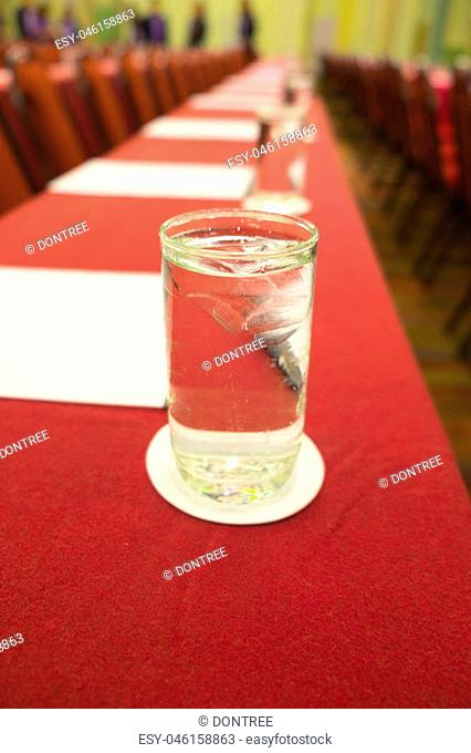 Close up glass on the red leather table in seminar room
